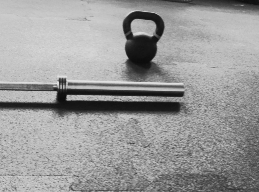 kettlebell and barbell on gym ground